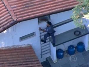 Policial tentando entrar na casa de um dos envolvidos. Foto TV Globo.