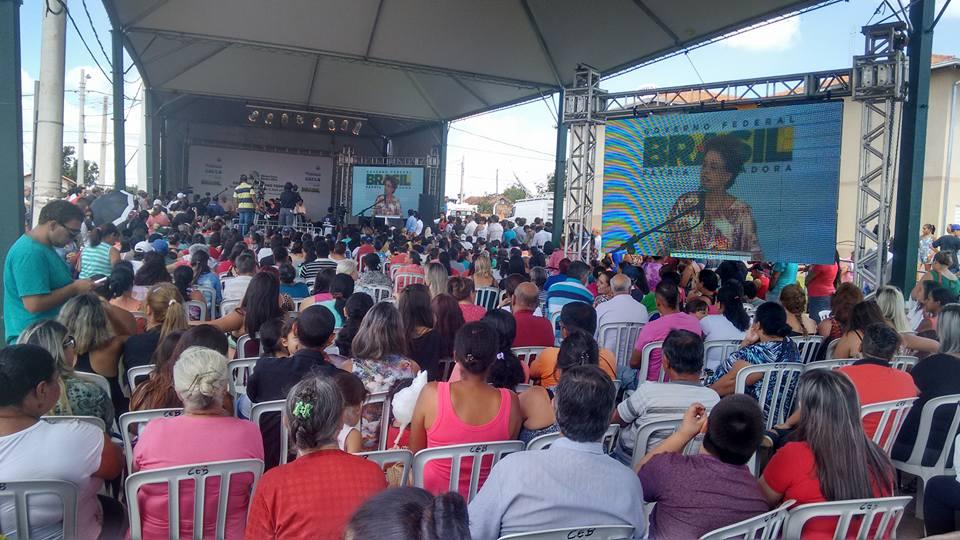 Beneficiados com os imóveis do MCMV, em Itapeva, e a presidente Dilma falando no telão.