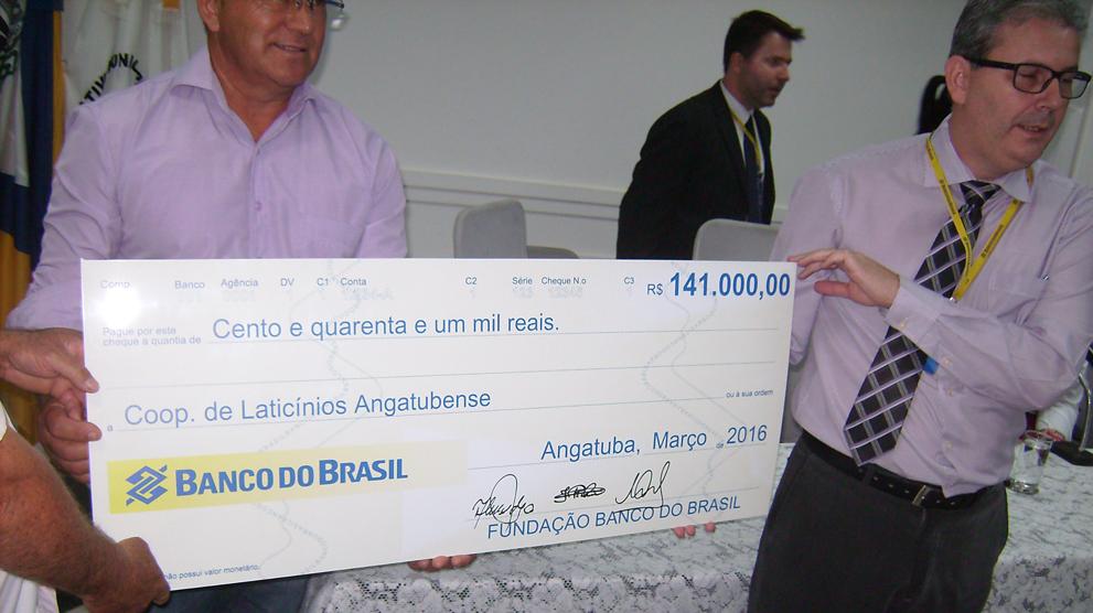 Gerente da agência do Banco do Brasil, de Angatuba, Rinaldo  Arena Câmara, à direita, com  segura o cheque simbólico.