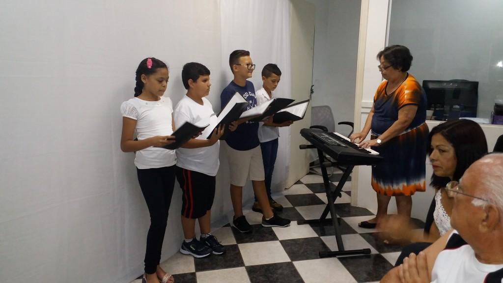 Professora Pérsides Fonda  e alunos apresentando número musical